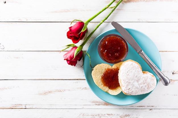 Desayuno de san valentín bollo en forma de corazón y mermelada de bayas, vista superior, espacio de copia