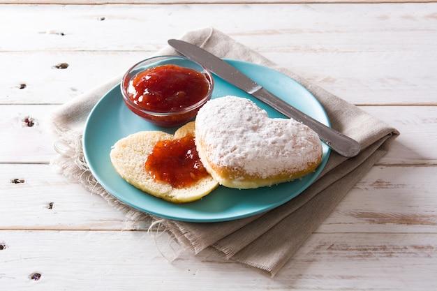 Desayuno de san valentín con bollo en forma de corazón y mermelada de bayas