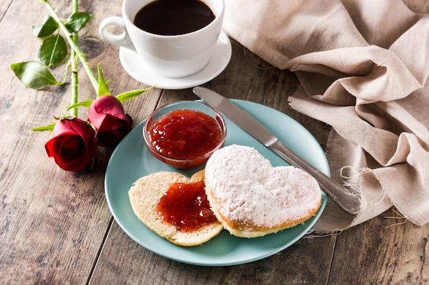 Desayuno de san valentín con café bollo en forma de corazón y mermelada de bayas