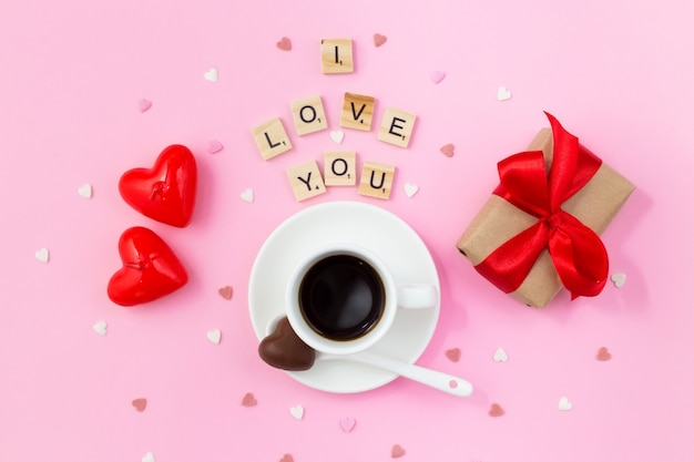 Desayuno de san valentín. taza de café con dulces de chocolate, caja de regalo con un lazo rojo y velas en rosa