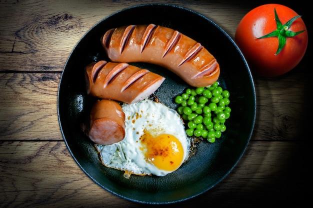 Desayuno en una sartén de huevos fritos, salchichas, guisantes y tomates. vista desde arriba