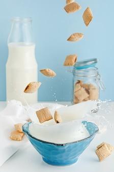 Desayuno seco de almohadillas de cereal de maíz con relleno de cacao y tazón azul de leche orgánica. concepto de levitación y comida voladora.