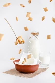 Desayuno seco de almohadillas de cereal con relleno de cacao en un tazón de arcilla roja con leche