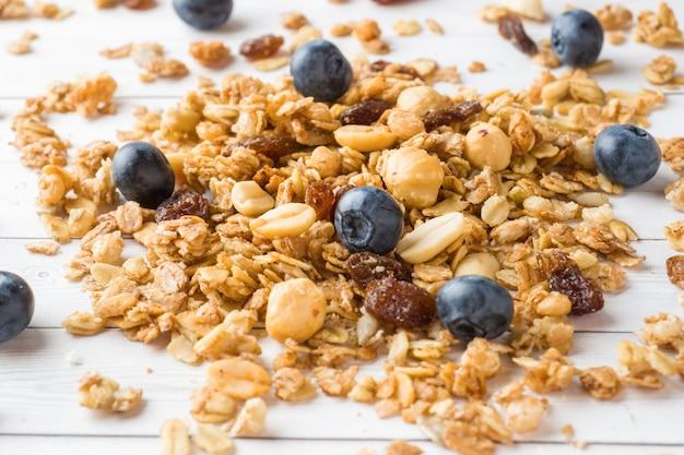 Desayuno seco de copos de avena, gránulos y frutos secos. muesli en una mesa de luz con arándanos