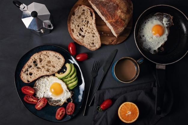 Desayuno servido con café, pan, huevos fritos, aguacate y tomates.