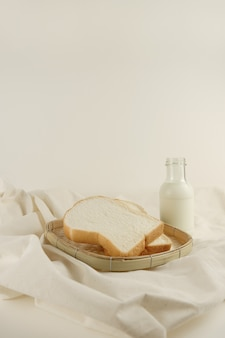 Desayuno set leche fresca y pan sobre fondo de lona