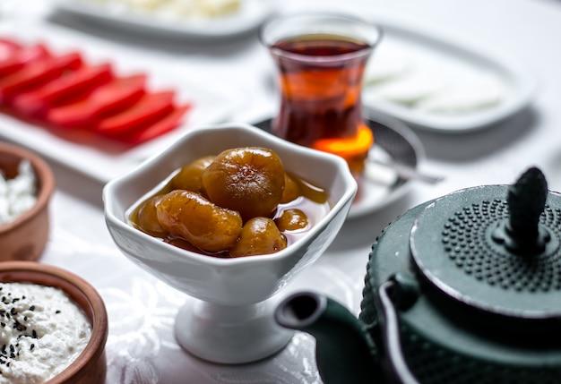 Desayuno set mermelada de higos en el tazón con té en vista lateral armudy