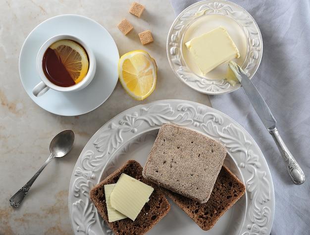 Desayuno simple té de limón y pan de centeno con mantequilla