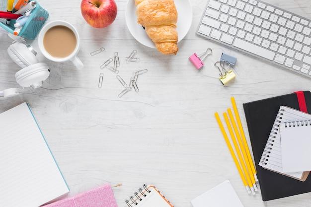 Desayuno; stationeries y teclado en el escritorio de madera