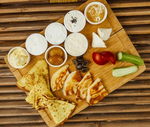 Desayuno tablero de madera con crepes, miel, queso crema, verduras y confitura.
