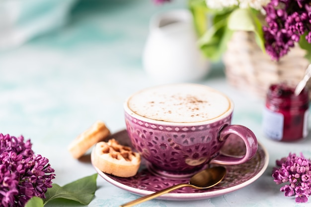 Desayuno taza de café, gofres, leche y crema y flores de color lila. mañana