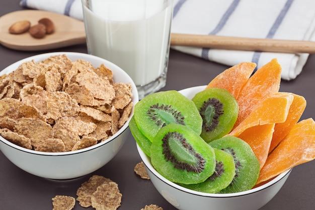 Desayuno. tazones con hojuelas de maíz, kiwi seco y mango. vaso de leche. alimentación saludable.