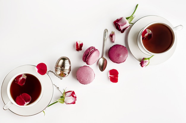 Desayuno té en mesa blanca con rosas y macarons