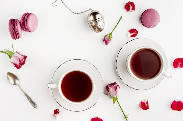 Desayuno té en mesa blanca con rosas y macarrones