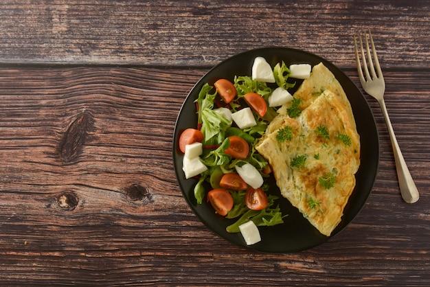 Desayuno - tortilla de huevo con tomate cherry, mozzarella y verde. mesa de madera con espacio de copia.