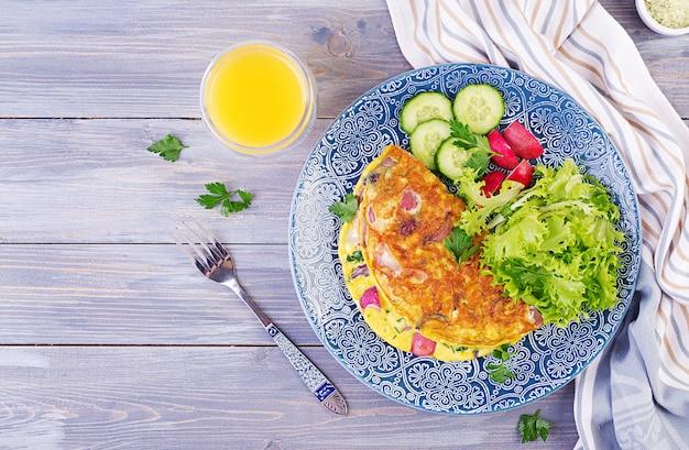 Desayuno. tortilla con rábano, cebolla roja y ensalada fresca en plato azul. frittata - tortilla italiana. vista superior