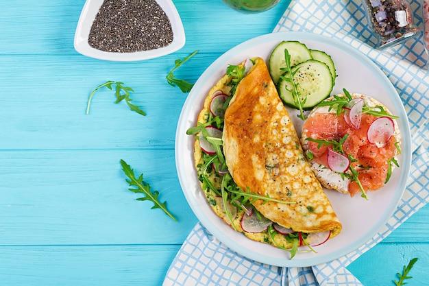 Desayuno. tortilla con rábano, rúcula verde y sandwich con salmón en plato blanco