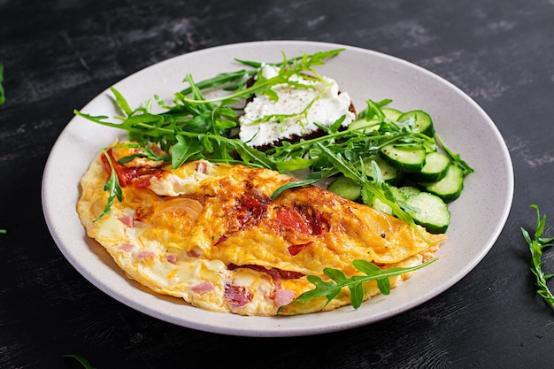 Desayuno. tortilla con tomate, queso y ensalada en un plato blanco. frittata - tortilla italiana.