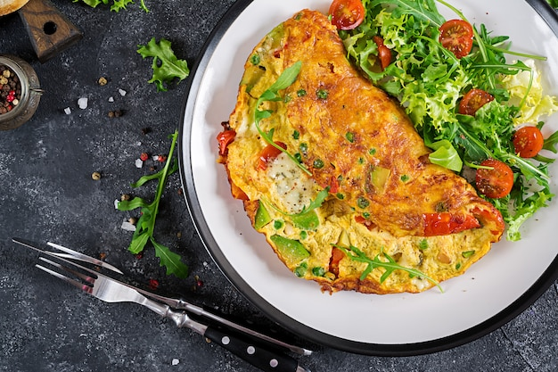 Desayuno. tortilla con los tomates, el aguacate, el queso azul y los guisantes verdes en la placa blanca.