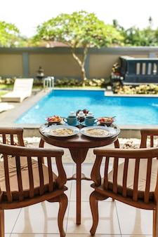 Desayuno tradicional balinesse con dos tazas azules de bebida caliente en la mesa de madera