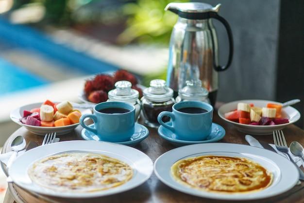Desayuno tradicional balinesse con dos tazas azules de bebida caliente en la mesa de madera.