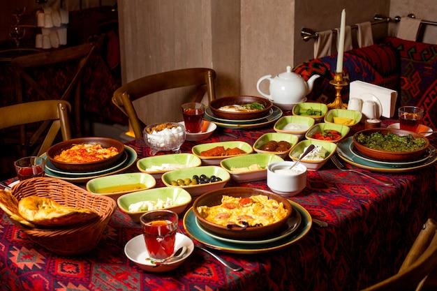 Desayuno tradicional con huevos y té negro, queso, mantequilla, miel, pepino, tomate y mermeladas.