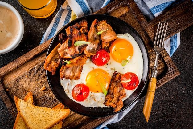Desayuno tradicional inglés casero, huevos fritos, tostadas, tocino, con taza de café y jugo de naranja.