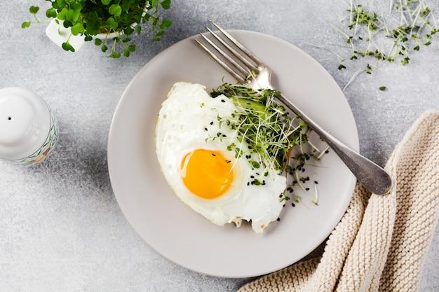 Desayuno tradicional inglés con huevos fritos en plato de cerámica sobre fondo de hormigón gris