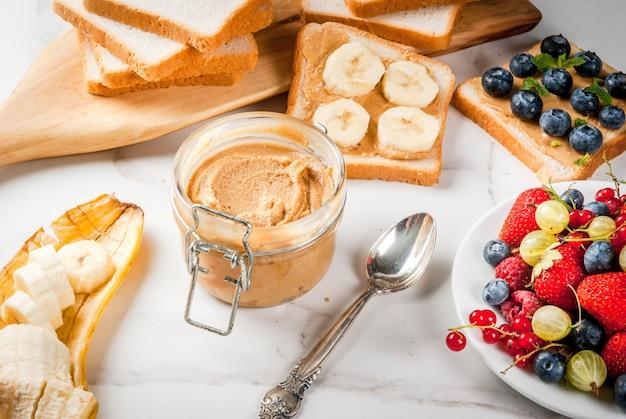 Desayuno tradicional de verano americano y europeo: sándwiches de pan tostado con mantequilla de maní, bayas, frutas manzana, durazno, arándano, arándano, fresa, plátano. mesa de mármol blanco. copyspace