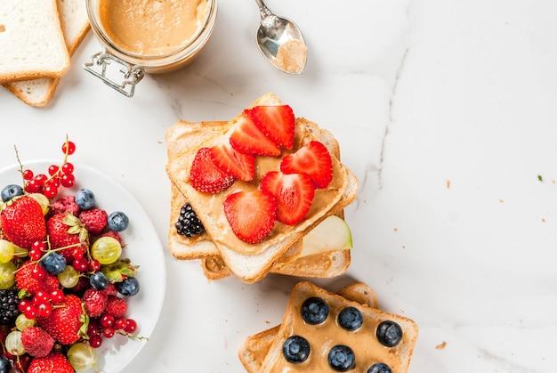 Desayuno tradicional de verano americano y europeo: sándwiches de pan tostado con mantequilla de maní, bayas, frutas manzana, durazno, arándano, arándano, fresa, plátano. mesa de mármol blanco. vista superior de copyspace