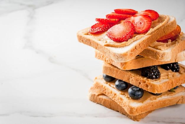 Desayuno tradicional de verano americano y europeo: sándwiches de pan tostado con mantequilla de maní, bayas, frutas manzana, durazno, arándano, arándano, fresa, plátano. mesa de mármol blanco.