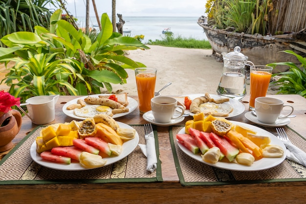 Desayuno tropical de fruta, café y huevos revueltos y panqueques de plátano.
