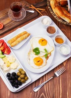 Desayuno turco con huevos fritos, tomate, pepino, quesos, aceitunas negras, miel, mermelada, queso crema, pan galeta y vaso de té.