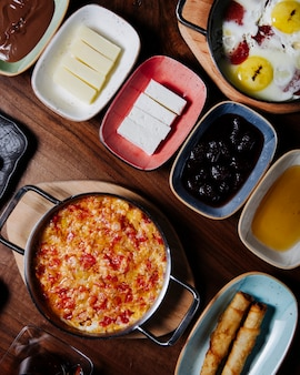 Desayuno turco con menemen, huevos fritos, queso, aceitunas, miel y mantequilla.
