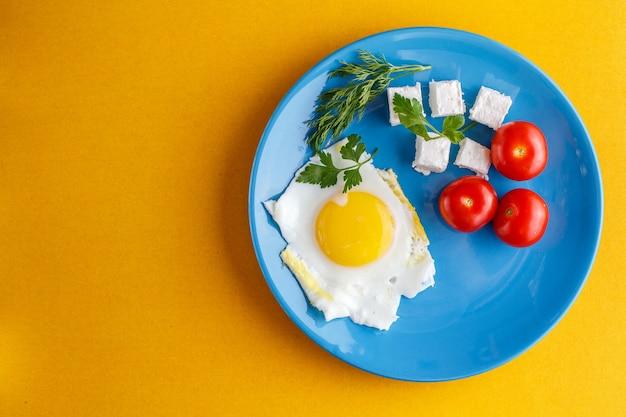 Desayuno turco en una placa azul sobre una superficie amarilla brillante