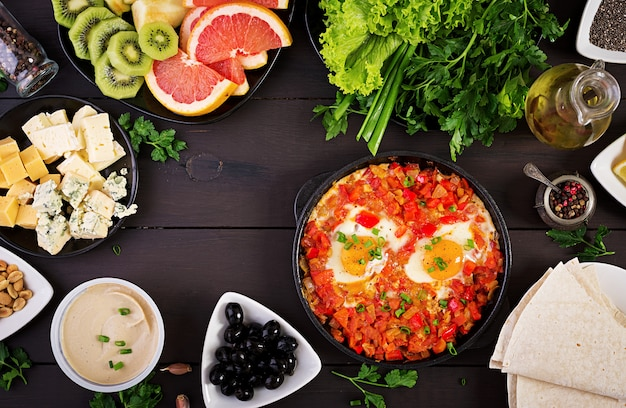 Desayuno turco .shakshuka, aceitunas, queso y fruta.