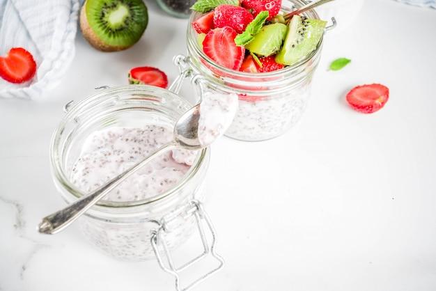 Desayuno vegetariano dietético saludable, yogur con semillas de chía y frutas frescas, fresas, kiwi, espacio de copia de fondo de mármol blanco
