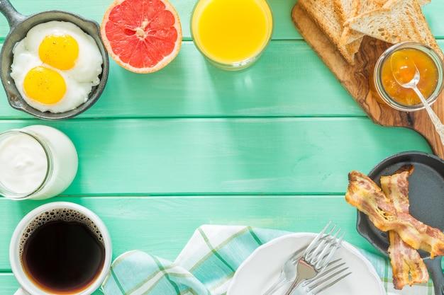 Desayuno de verano: huevos, tocino, tostadas, mermelada, café, jugo