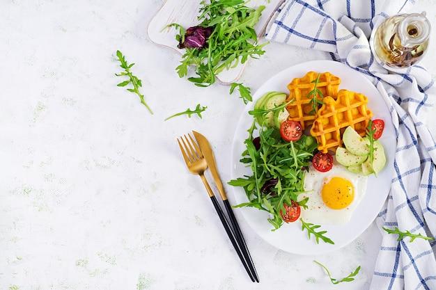 Desayuno con waffles de calabaza, huevo frito, tomate, aguacate y rúcula sobre superficie blanca