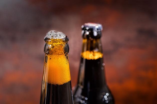 Desbordamiento de cerveza de una botella de cerveza recién abierta. concepto de alimentos y bebidas