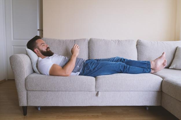 Descalzo hipster acostado en el sofá con teléfono inteligente