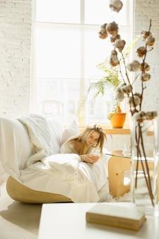 Descansando en casa. hermosa mujer joven acostada en el sofá en casa con luz solar cálida.