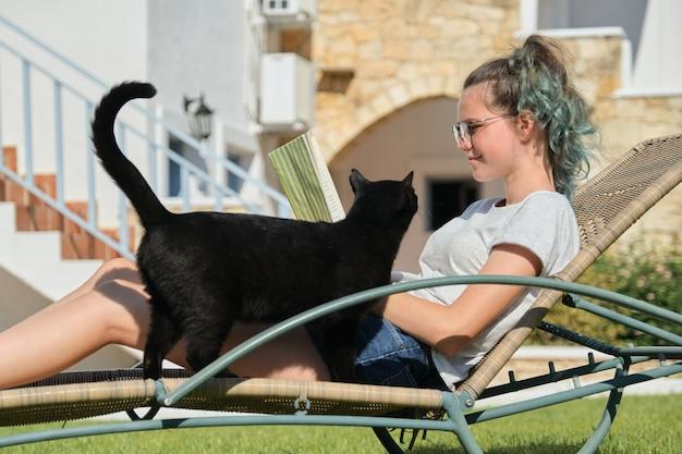 Descansando niña adolescente libro de lectura con gato doméstico negro