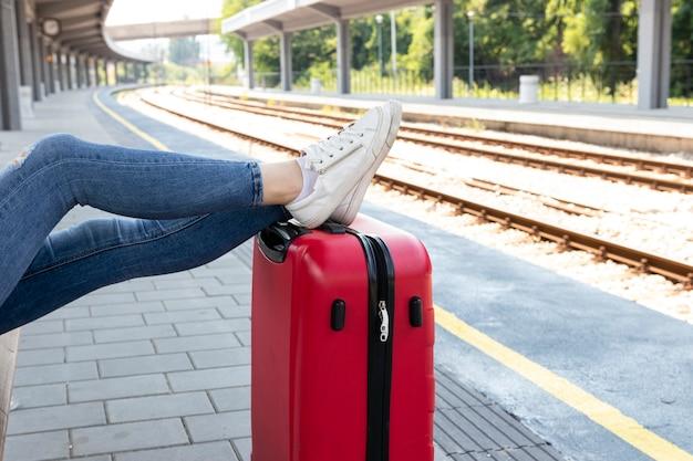 Descansando las piernas sobre el equipaje en la estación de tren
