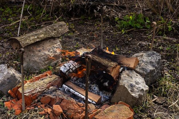 Descansar en el jardín en la naturaleza, preparar un fuego para hacer una barbacoa, fuego de madera de cerezo.