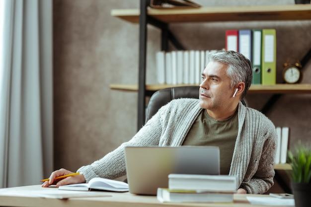 Descansar del trabajo. bonito hombre pensativo mirando por la ventana mientras descansa del trabajo