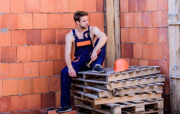 Descanse para relajarse. trabajador atractivo. trabajador sexy. construcción de edificio. trabajador de reparación de mantenimiento general. fondo de pared de ladrillo trabajador. el hombre construye su propia casa. realiza tareas básicas. concepto de masculinidad.