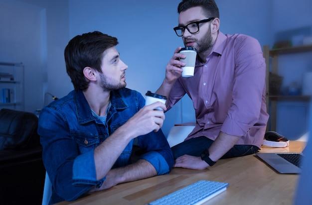 Descanso. atractivo hombre barbudo agradable tomando café y hablando entre sí mientras toma un descanso del trabajo
