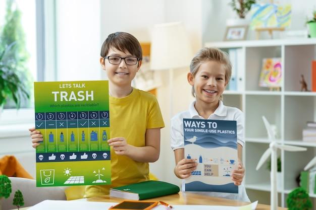 Descanso entre clases. orgullosos y alegres niños mostrando carteles informativos sobre los principios del estilo de vida ambiental