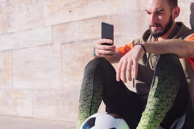 Descanso de jugador de fútbol consultando su teléfono inteligente